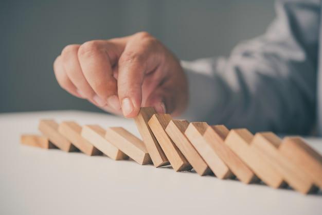 Geschäftsmannhand, die das hölzerne effektkonzept des dominos für geschäft stoppt.