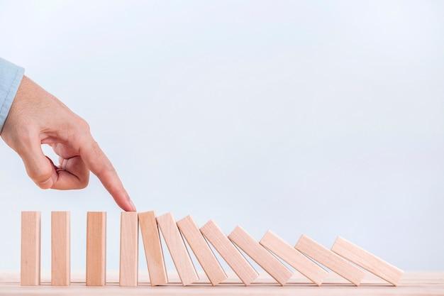 Geschäftsmannhand, die den dominoeffekt für management und lösung stoppt