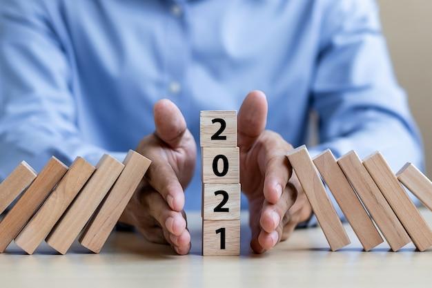 Geschäftsmannhand, die den fall von 2021 stoppt