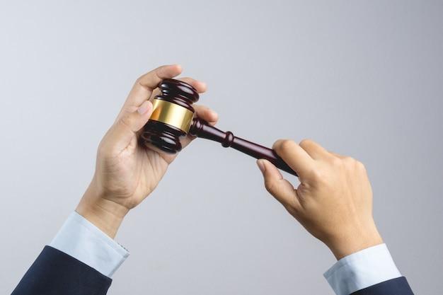 Geschäftsmannhand, die den hammer des hölzernen richters als gesetzes- oder gerechtigkeitszeichen hält