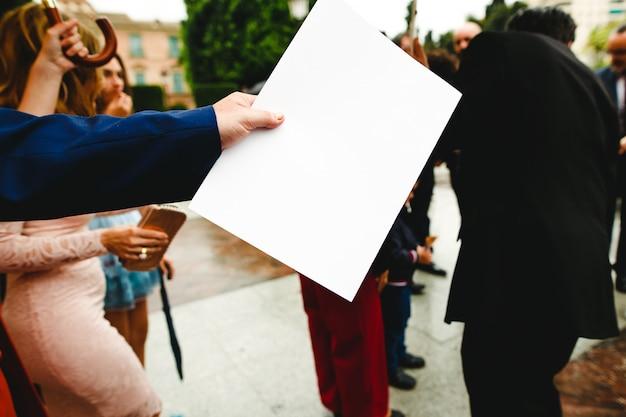 Geschäftsmannhand, die ein leeres papier mit wichtigen informationen übergibt