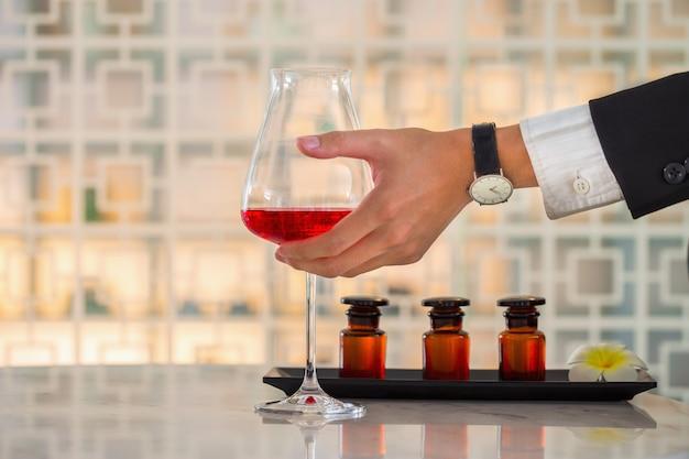 Geschäftsmannhand, die ein rotweinglas auf tabelle hält