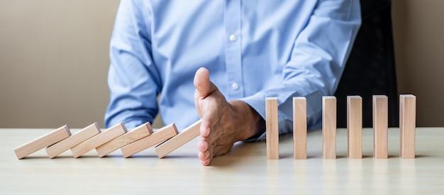Geschäftsmannhand, die fallende holzklötze oder dominos stoppt