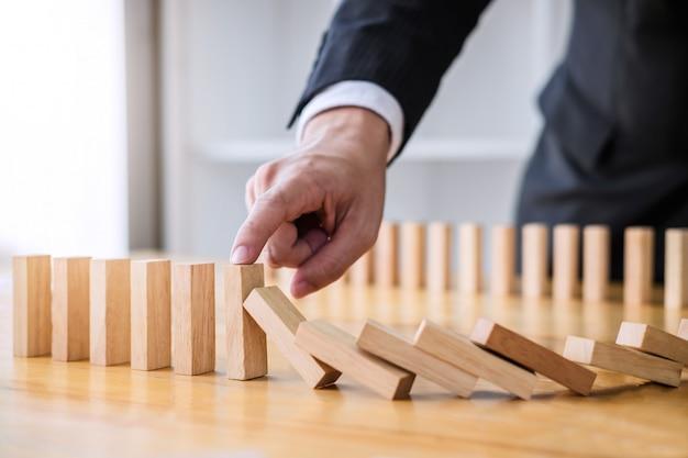 Geschäftsmannhand, die fallenden hölzernen dominoeffekt vom ununterbrochenen gestürzt oder vom risiko stoppt