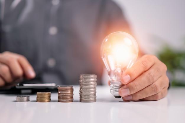 Geschäftsmannhand, die glühbirne mit berechnung und geldstapel hält idee zum energiesparen
