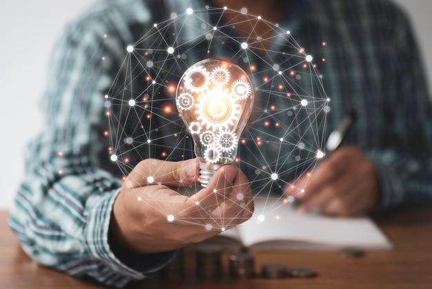 Geschäftsmannhand, die glühbirne mit orange leuchtendem und verbindungslinie hält. kreatives denken ideenkonzept.