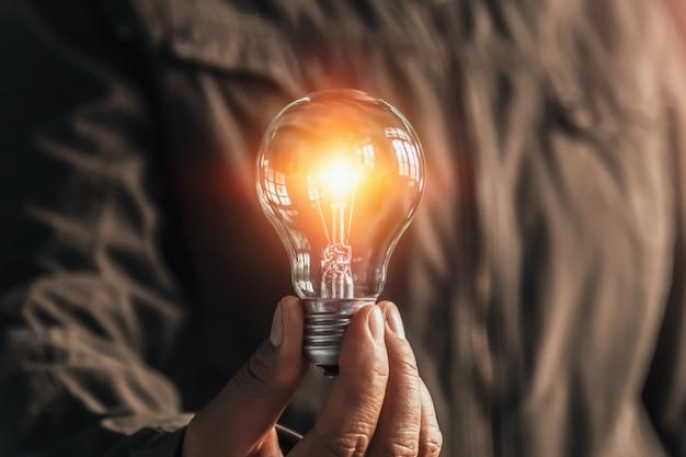 Geschäftsmannhand, die glühlampe hält. idee alternative energiesparende elektrizität