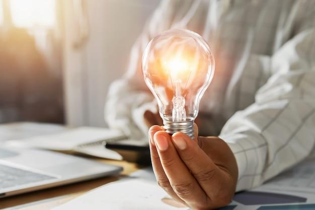 Geschäftsmannhand, die glühlampe im büro hält. konzept energie sparen strom