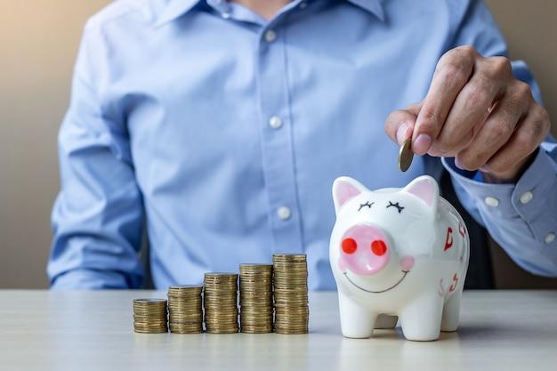 Geschäftsmannhand, die goldene münze auf piggy bankverkehr setzt
