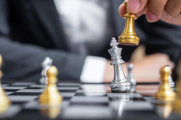 Geschäftsmannhand, die goldene schachkönigfigur und schachmatt-feind oder gegner während des schachbrettwettbewerbs bewegt.