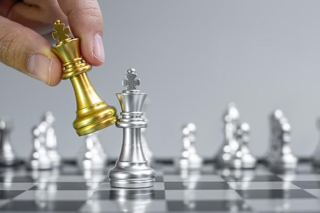 Geschäftsmannhand, die goldschachkönigfigur während des schachbrettwettbewerbs bewegt.
