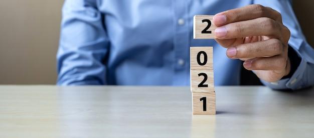Geschäftsmannhand, die hölzerne würfelblöcke mit 2021 hält