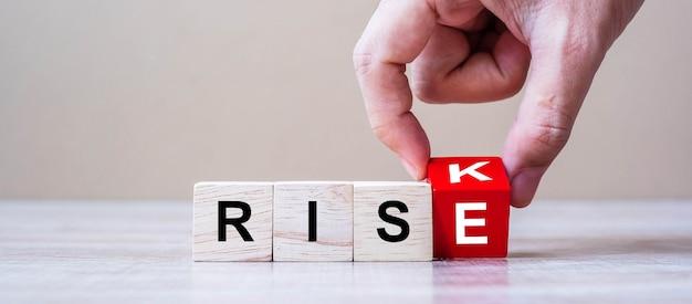 Geschäftsmannhand, die hölzerne würfelblöcke mit risiko ändern, ändern zu rise-text