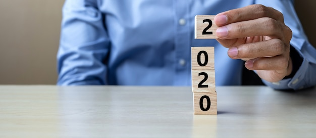 Geschäftsmannhand, die hölzernen würfel mit wort 2020 auf tabelle hält