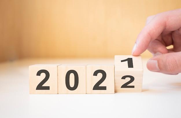 Geschäftsmannhand, die holzwürfel mit flip-over-block 2021 bis 2022 hält, plant wort auf tischhintergrund.