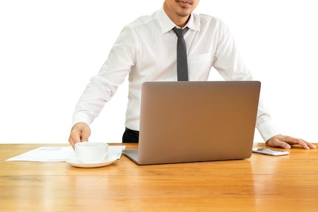 Geschäftsmannhand, die kaffeetasse mit laptop auf hölzernem schreibtisch im beschneidungspfad hält