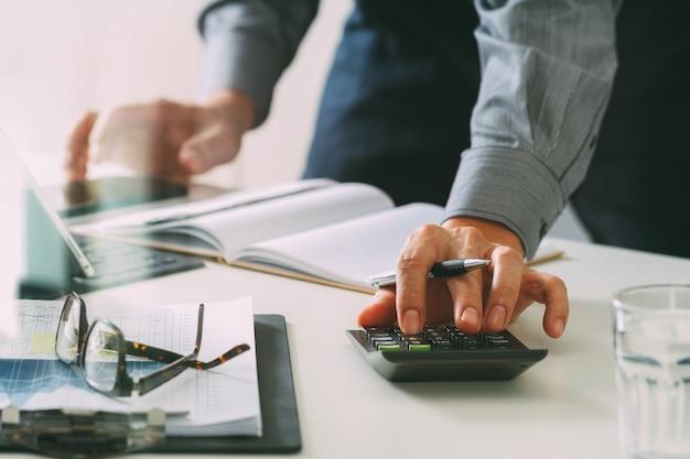 Geschäftsmannhand, die mit finanzen über kosten und taschenrechner und latop arbeitet