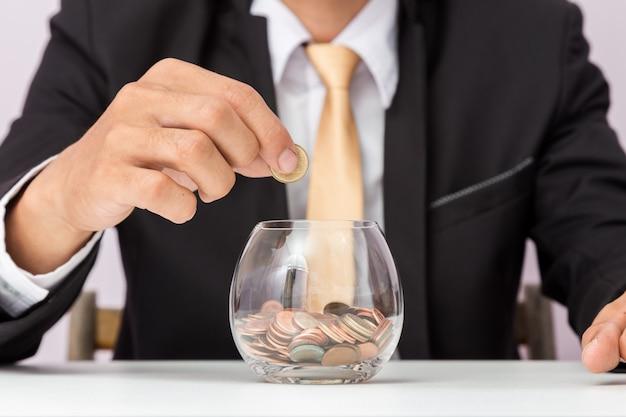 Geschäftsmannhand, die münzen auf das glas setzt,