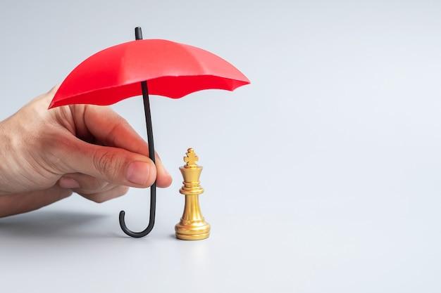 Geschäftsmannhand, die rote regenschirmabdeckung schachkönigfigur hält