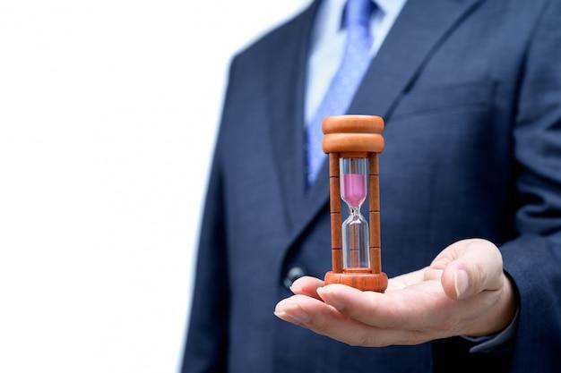 Geschäftsmannhand, die sanduhr hält, zeitmanagementkonzept.