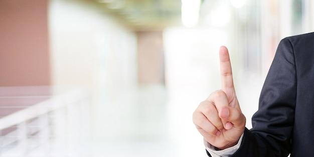 Geschäftsmannhand, die über unschärfebürohintergrund, geschäftshintergrund sich berührt