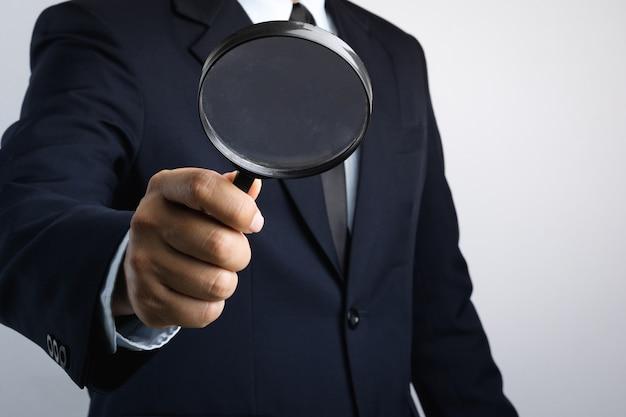Geschäftsmannhand, die vergrößerungsglas für inspektion hält