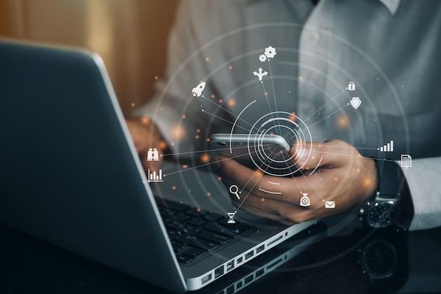 Geschäftsmannhand mit handy und laptop-computer mit digitalem schichteffekt. big data analytics mit business intelligence (bi) konzept.