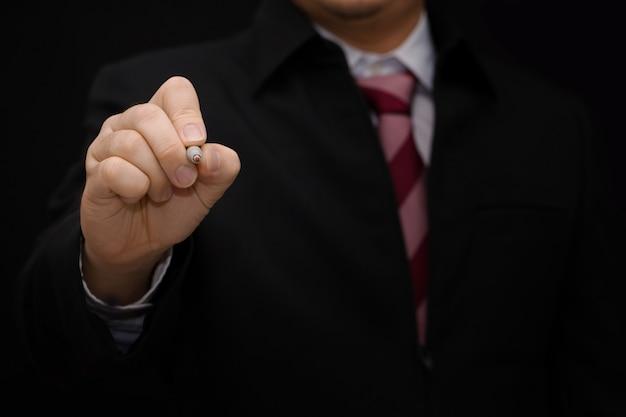 Geschäftsmannhand schreibt auf dem bildschirm auf schwarzem hintergrund