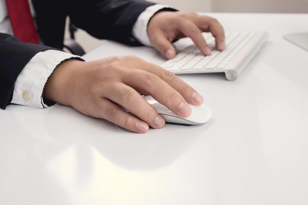 Geschäftsmannhand unter verwendung der computermaus