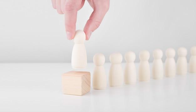 Geschäftsmannhand wählen hölzernen geschäftsmann, der von der menge abhebt