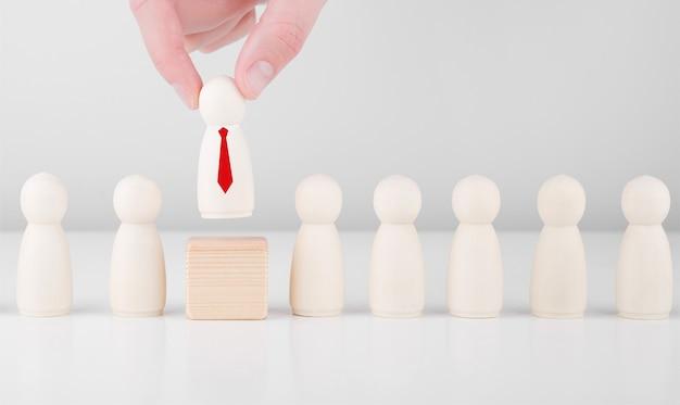Geschäftsmannhand wählen hölzernen mann in einer roten krawatte, die von der menge abhebt.