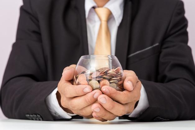 Geschäftsmannhand, welche die münzen auf das glas, konzept des einsparungsgeldes für finanzbuchhaltung setzt