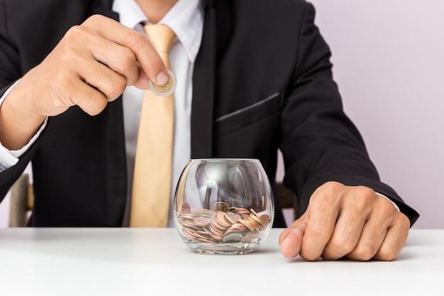 Geschäftsmannhand, welche die münzen auf das glas, konzept des sparens des geldes für finanzbuchhaltung setzt