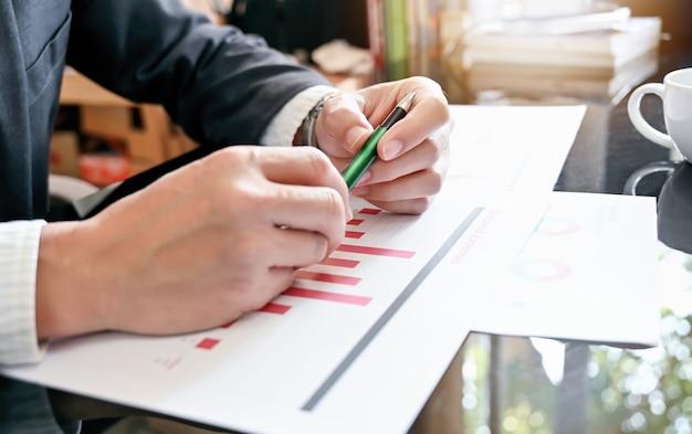 Geschäftsmannhandbehälter beim arbeiten mit papierdokument im büro.