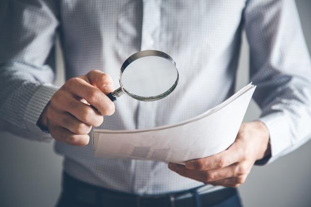 Geschäftsmannhanddokument und lupe im büro