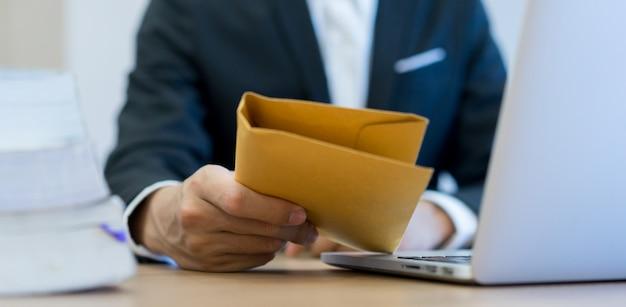 Geschäftsmannhandholding und senden geheimen tan umschlag
