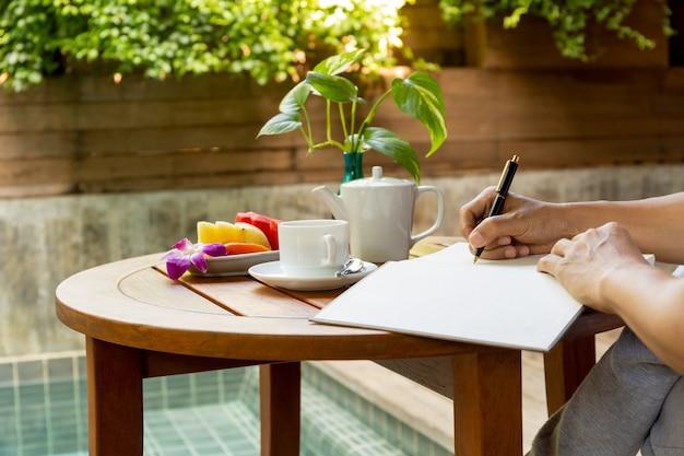 Geschäftsmannhandschrift im notizbuch auf hölzerner tabelle mit kaffeetasse und frischer frucht auf vaca