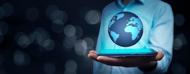 Geschäftsmannhandtelefon mit globus im bildschirm