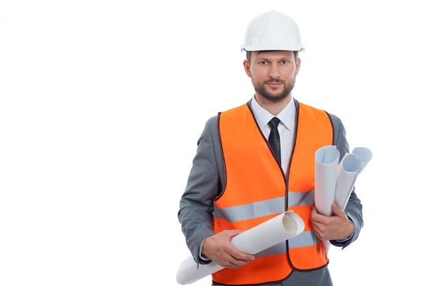 Geschäftsmanningenieur, der bauplanpläne hält, die auf weißem tragendem helm und orange sicherheitsweste aufwerfen