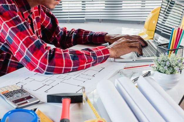 Geschäftsmanninnenarchitekt, der daten mit laptop-computer bearbeitet und bespricht