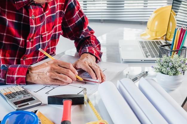 Geschäftsmanninnenarchitekt, der mit plan und architekturprojekt arbeitet und zeichnet
