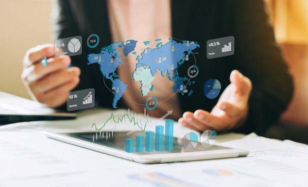 Geschäftsmanninvestition, die unternehmensfinanzbericht mit digitalen diagrammen analysiert.