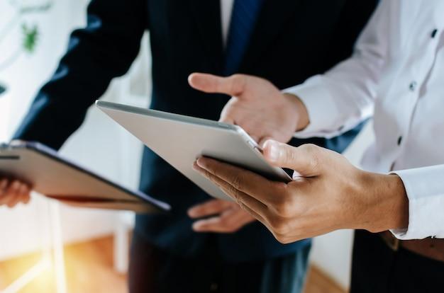 Geschäftsmanninvestor mit zwei jungen, der informationen über finanzstatistik spricht und liest