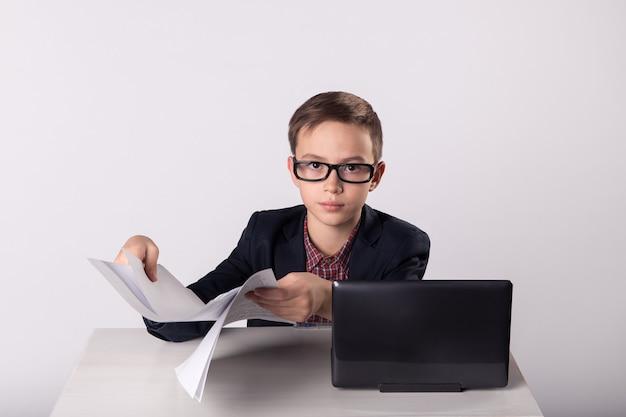 Geschäftsmannkind, das rohlinge in seinen händen hält