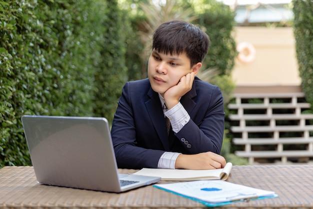 Geschäftsmannkonzept ein junger geschäftsmann im marineanzug sitzt im garten mit den dokumenten und dem laptop auf dem tisch, der nachdenklich und ernst aussieht.