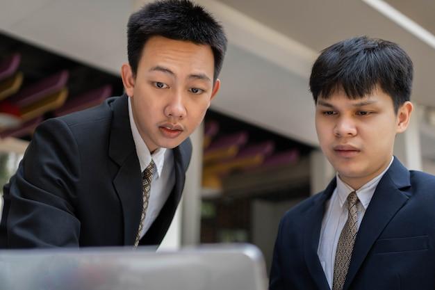 Geschäftsmannkonzept zwei geschäftsleute, die offizielle anzüge tragen, genießen die teilnahme und lösen probleme im projektplan.
