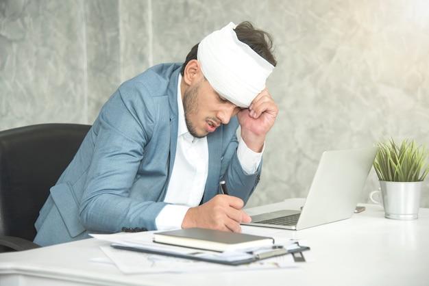 Geschäftsmannkopfschmerzen und -verband von der arbeitsverletzung am arbeitsplatz