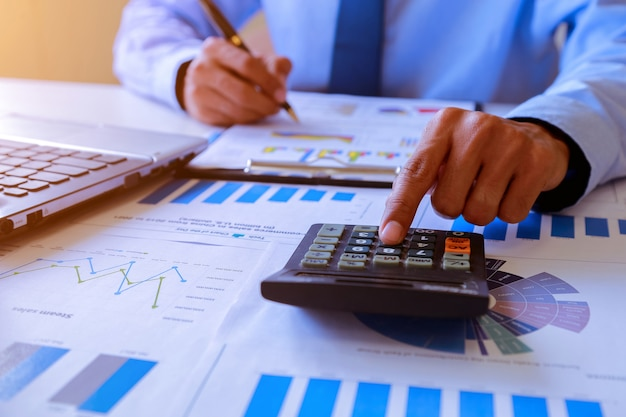 Geschäftsmannleute, die analysierend arbeiten und zusammenfassung berechnen