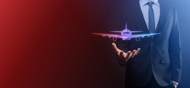 Geschäftsmannmann, der eine flugzeugflugzeugikone in seinen händen hält. online-ticketkauf. reisesymbole über reiseplanung, transport, hotel, flug und reisepass. flugkarten-buchungskonzept.