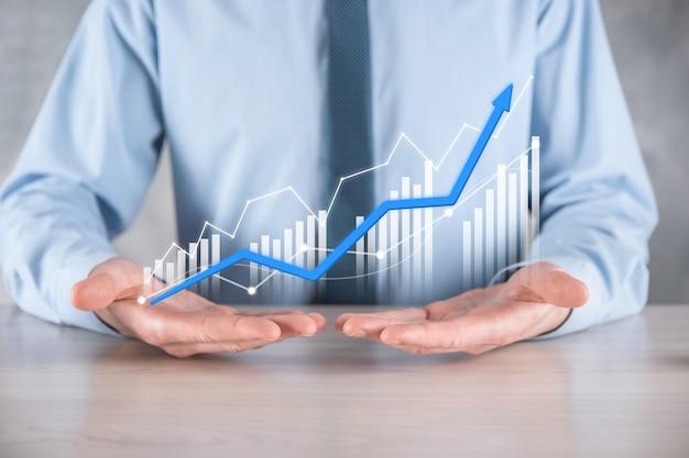 Geschäftsmannmann, der eine grafik mit positivem gewinnwachstum hält. planen sie das wachstum der grafik und die steigerung der positiven indikatoren in seinem geschäft. profitabler und wachsender.